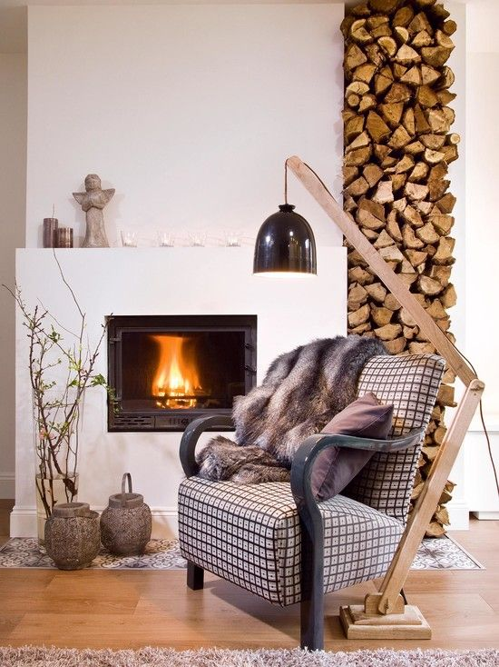 Comfy-looking seating area in front of a lit fireplace with stacks of firewood at the ready. So cozy!