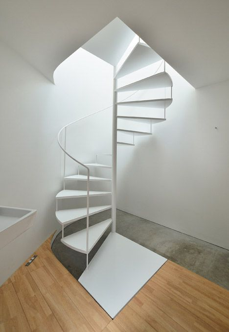 A white spiral staircase with a slender handrail winds through each of these apartments from an entrance hall and bathroom at ground level, to a living area on the first floor and a mezzanine bedroom sitting below the sloping roof.