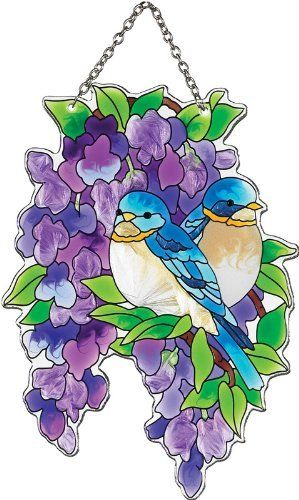 Joan Baker Designs SSD1034 Bluebirds and Wisteria Art Glass Suncatcher by Joan Baker Designs. $21.00. Water-cut fired glass. Vivid translucent color for window display. Hand-painted. Chain included for convenient hanging in a window. Two bluebirds rest in a densely blooming bough of lavender wisteria on this water-cut art glass Suncatcher.    For more than 40 years, Joan Baker Designs' talented artisans have created stunning decorative art glass items. Each piece is designe...