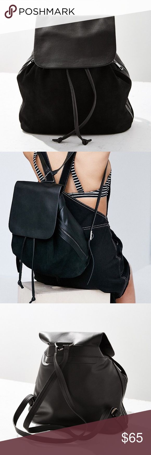 """Black suede backpack minimalist coachella festival Refresh your look with this sleek minimalist backpack, found exclusively at UO. Soft suede body with a spacious compartment and drawstring bucket cinched closure. Accented with faux leather paneling and buttoned flap-front with exposed zippered side pockets and skinny, adjustable shoulder straps.  Content + Care - Polyurethane, suede - Spot clean - Imported  Size - Length: 21.2"""" - Width: 5.51"""" - Height: 12.2"""" Urban Outfitters Bags Backpacks"""