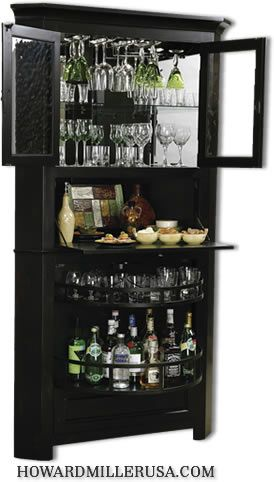 695082 Howard Miller wine storage cabinet. This large wine and spirit cabinet provides ample storage yet offers a space-saving corner design.The upper compartment feature heavily seeded glass panes in the front doors and contains an adjustable glass shelf.Lower drawer opens up to two-tiered nested bottle storage that houses up to 10 wine bottles.Finished in Worn Black with brown undertones on select hardwoods and veneers.Hanging stemware rack keeps stemware handy.Glass mirrored back