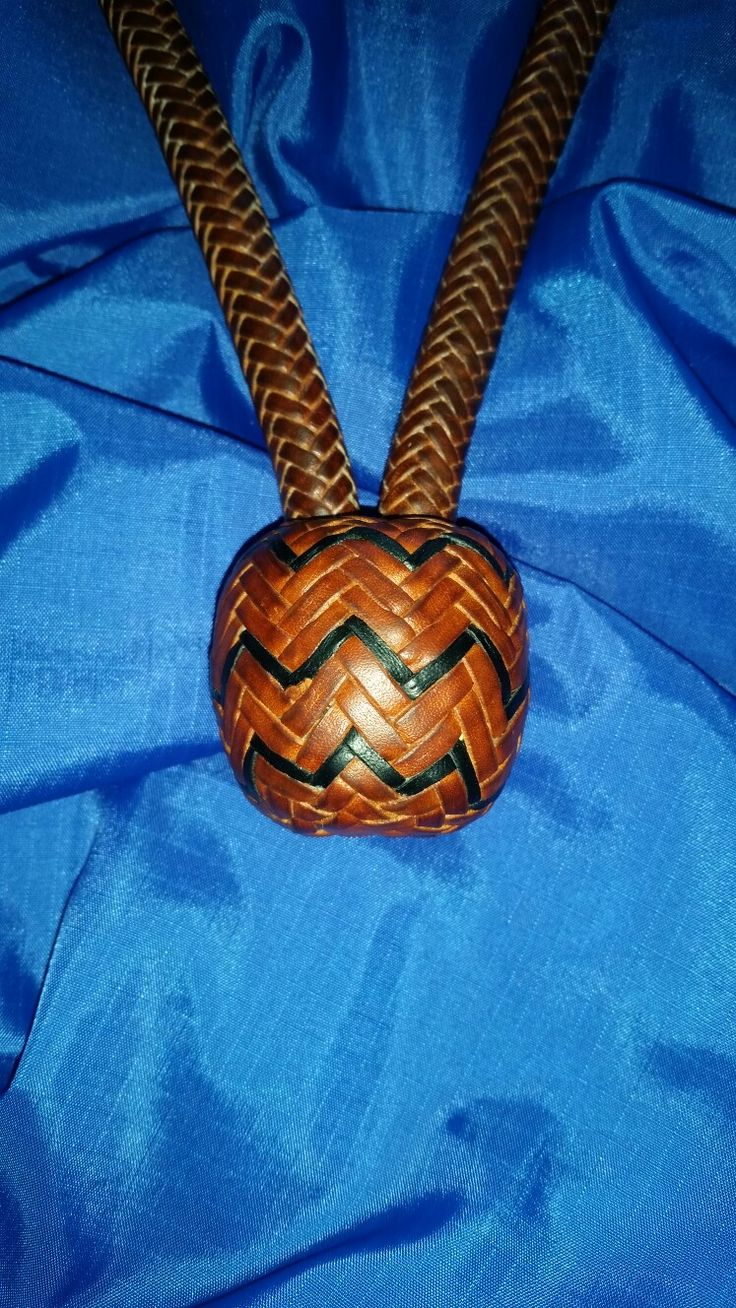 """Bosal 001.  7/16"""", 12 plait kangaroo hide over twisted rawhide core.  7.5"""" x 6 bight nose button, 10 3/4"""" inside length. Tan with black interweave."""