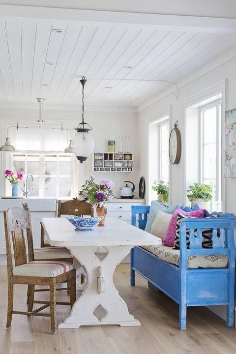SOMMERHYTTE: Slagbenken på kjøkkenet er et vakkert blikkfang som oser av sommer, fylt med puter fra Home&Cottage og Zanz. Benken er kjøpt brukt og har fått følge av arvede stoler.Bordet er et typisk norsk bondebord som er malt hvit. Kjøkkeninnredningen er fra Ikea. Over kjøkkenet ses annen etasje nesten som en hems, med flere soverom på rad | LEV LANDLIG