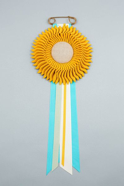 Golden Yellow with light blue, cream, golden yellow & sage green tails. Natural linen centre. Vintage safety pin.