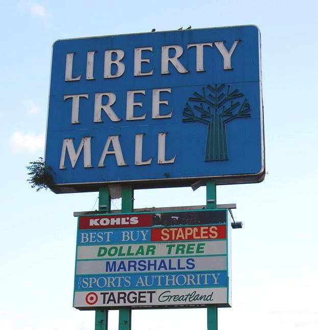 old liberty tree mall sign, compete with tree growing out of it.
