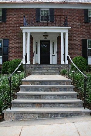 Fieldstone risers capped with flagstone lead to wide portico topped with flat roof porch with wrought iron railings