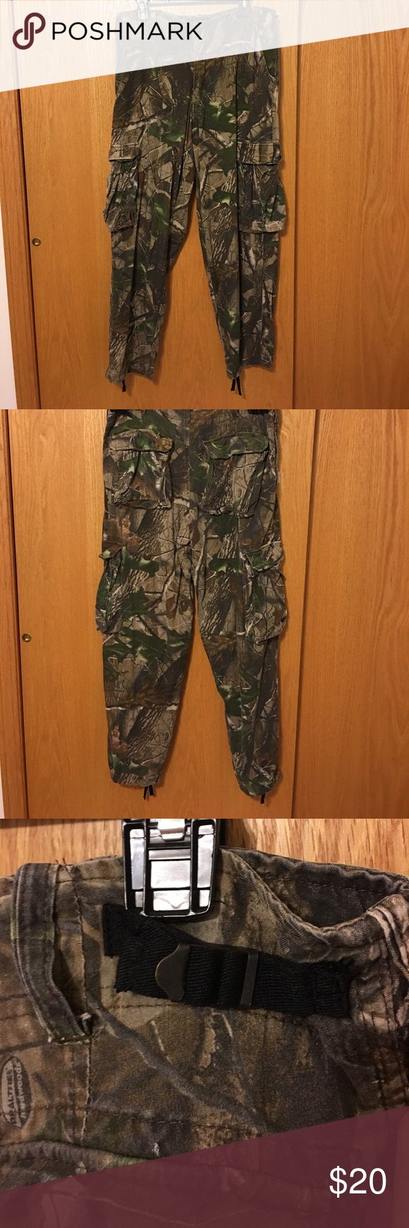 """Redhead men's rayon Camo cargo pants Medium Men's camouflage pants size medium. Waist adjusts from about 32"""" up to about 38"""" with cinches on back of waist. Zip fly and button closure, belt loops and hip pockets, including a hidden pocket on right hip. Large side pockets near knees and back pockets with flap & button close. Drawstrings in ankle hem for wearing with boots. 100% rayon allows quiet movement. Real tree hardwood pattern. Lightweight for warmer days, room to layer over under armour…"""