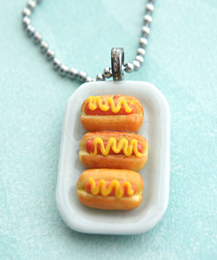 This necklace features a miniature platter pendant adorned with handmade hotdog sandwiches sculpted from polymer clay. The ceramic platter measures about 2 cm x 1.5 cm and is securely attached to a si
