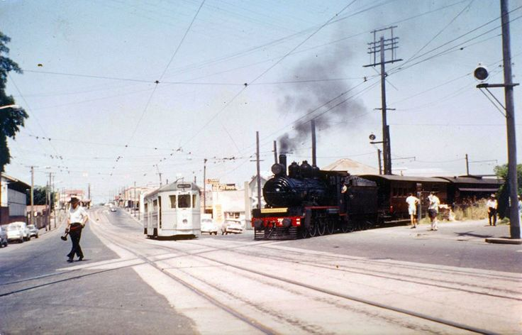 Man ring's the bell leading the Train across Stanley Street at the Woolloongabba 5 ways. FM Tram waits for the road to clear!