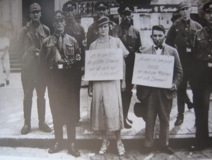 """Немецкая женщина и ее муж-еврей выставлены у позорного столба. На табличке на шее женщины написано """"Я - свинья и связалась с евреем"""", у мужа - про то, что он, еврей, посмел затащить в постель настоящую арийку."""