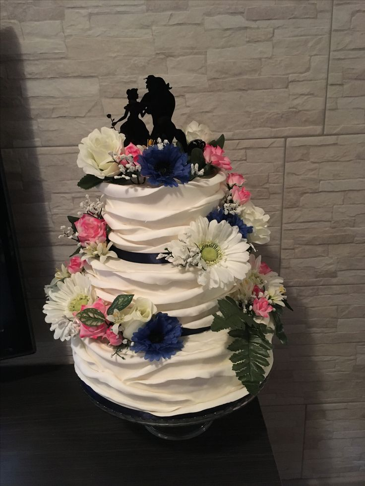 """Dolcissima wedding cake in stile floreale con topper """"la bella e la bestia"""" gerbere bianche, roselline rosa, gerbere blu e velo da sposa"""