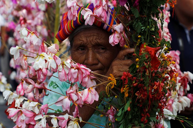A woman takes part in a procession during the celebration of the Palms and Flowers Festival in Panchimalco, El Salvador.
