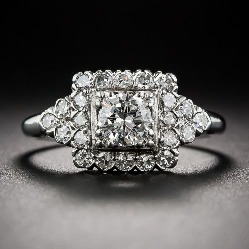 A fabulous and flashy platinum engagement ring from the fabulous and occasionally flashy nineteen fifties. A fiery ice-white round brilliant-cut diamond, weighing .45 carats, blazes from atop a glittering frame of single-cut diamonds with a twinkling trio shining on on each shoulder. Classic 'fishtail' settings of the period adorn the sides of this vintage smile-maker.