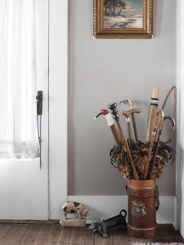 The owner's collection of walking sticks and feather dusters finds a home in an English-leather fire bucket from the late 1800s in this Indiana farmhouse. The midcentury pig doorstop and dachshund boot scraper are both made of cast iron.