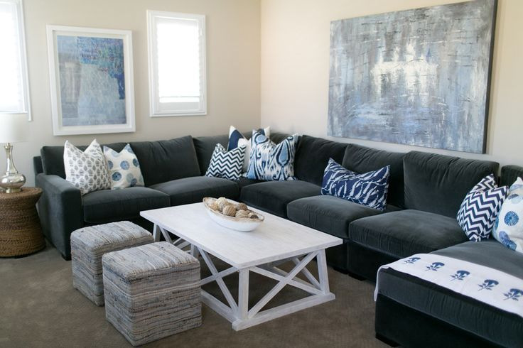 Amazing living room features a a blue and grey abstract art piece placed above a dark grey velvet ...
