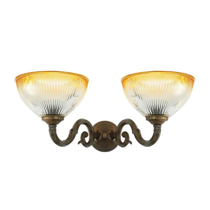 The Tawau wall light is a traditional two-arm wall light featuring two brass spiralling arms that each hold an up lit amber rimmed Holophane glass shade, creating an old-world feel.