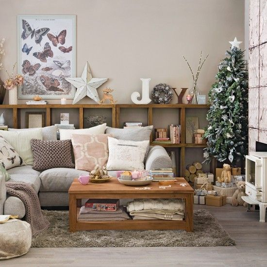 This festive living room is kept calm and cosy with faux foliage, natural wood decorations, super-soft cushions and chunky knits throws
