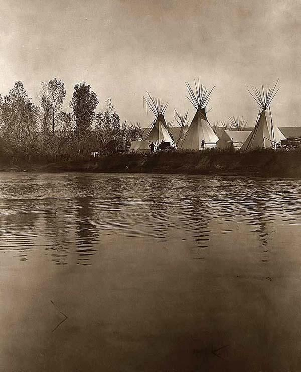 A one-of-a-kind photograph of authentic Indian Tepees. It was created in 1908. The photograph illustrates an original Crow Indian Camp. The picture shows many Tepees, tents, wagons, and horses. Men can be seen on the distant shore of the river.
