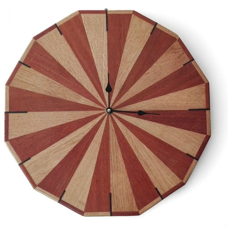Twelve-sided wall clock. Dodecagonal wall clock inlaid by hand, composed of 24 triangles of various wood types.