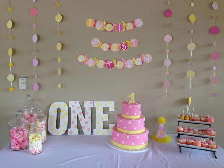 pink and yellow polka dot first birthday cake table