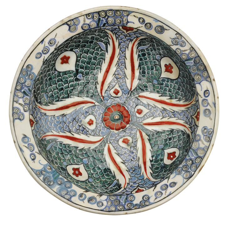 AN IZNIK POLYCHROME POTTERY DISH, TURKEY, CIRCA 1580-85 of shallow round form, decorated in underglaze green, blue and relief red, with a central flower emanating saz leaves set on a fish-scale ground, the rim with a breaking-wave motif, alternating tulips and flowerhead motifs to underside 30cm. diam.