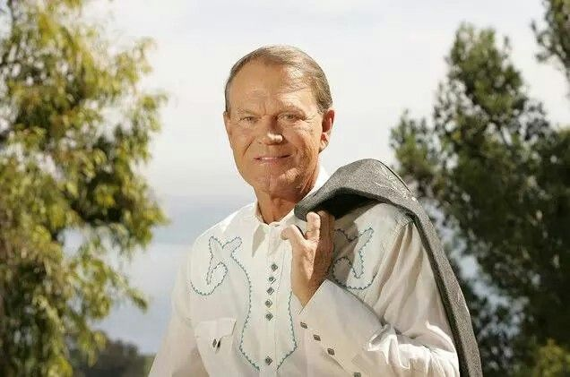 """Country singer/songwriter/actor Glen Campbell, died on August 8th 2017 from complications of Alzheimer's Disease. Campbell was popular during the 60s for his songs such as, """"Gentle On My Mind"""", """"Galveston"""" and """"Wichita Lineman"""", but his role in the movie, """"True Grit"""" expanded his popularity into the 70s. He recorded """"Southern Nights"""" and his biggest hit, """"Rhinestone Cowboy""""."""