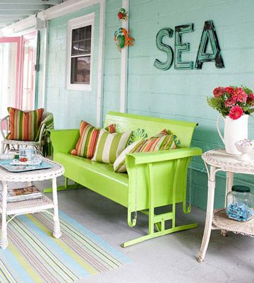 An 0ld glider is painTed margariTa green. White wicKer side chairs and Tables highlight the glider, making it the porch's focal point. Vintage letters match the mint-green walls. Colorful pillows and an area rug add comfort and complete the look.