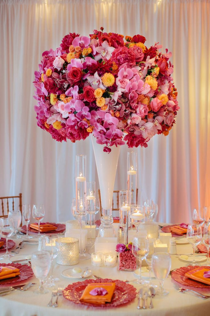 White guest tables were topped with a towering centerpiece comprised a multitude of flowers in various shades of pink, yellow, and orange. #centerpiece Photography: Clane Gessel Photography. Read More: http://www.insideweddings.com/weddings/tropical-spring-wedding-at-the-st-regis-princeville-in-hawaii/635/