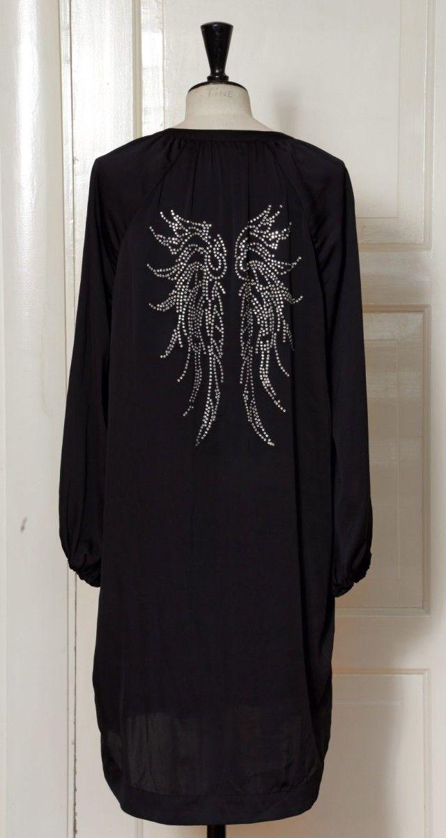 En ensfarget silkebluse kan få mer oppmerksomhet ved å stryke lekker rhinestone-dekor på ryggen,