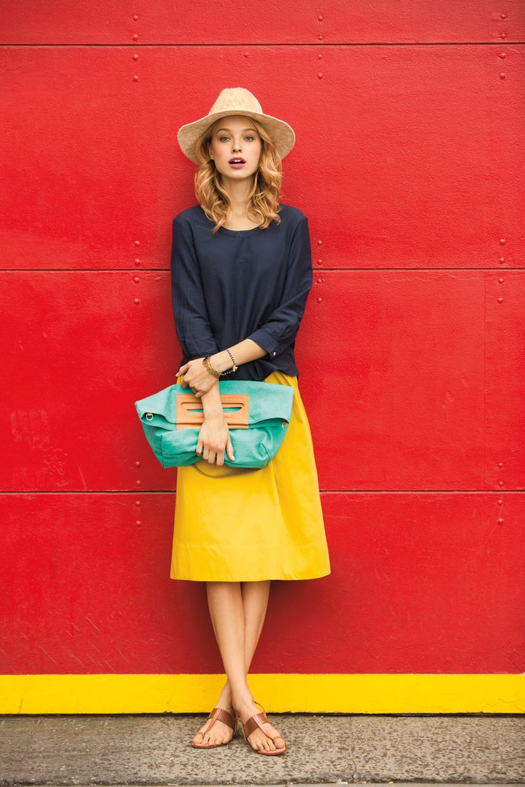 Basics in pop colors. Knee length bright yellow a-line skirt, loose navy sweater, hat, teal bag, simple leather sandals