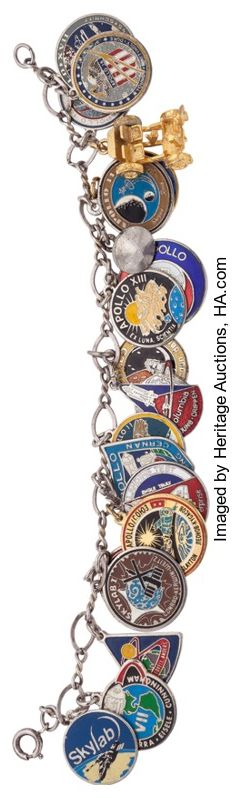 """NASA Apollo - Space Shuttle Charm Bracelet, 1968-1981. A 7"""" long silver bracelet bearing approximately eighteen enameled charms, 0.5"""" or slightly larger. Missions represented include all the manned Apollo flights, Apollo-Soyuz, Skylab, STS ALT, STS-1, as well as an Apollo capsule and LRV. Appears to have been collected during the period. Shows light wear, very good. ..."""