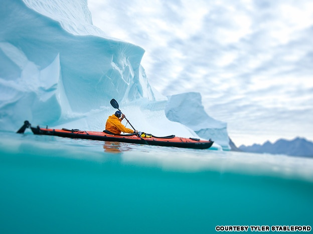 At the Arctic Circle, Thorsten Henn kayaks amid icebergs in the fjords of eastern Greenland.  via CNN 2013