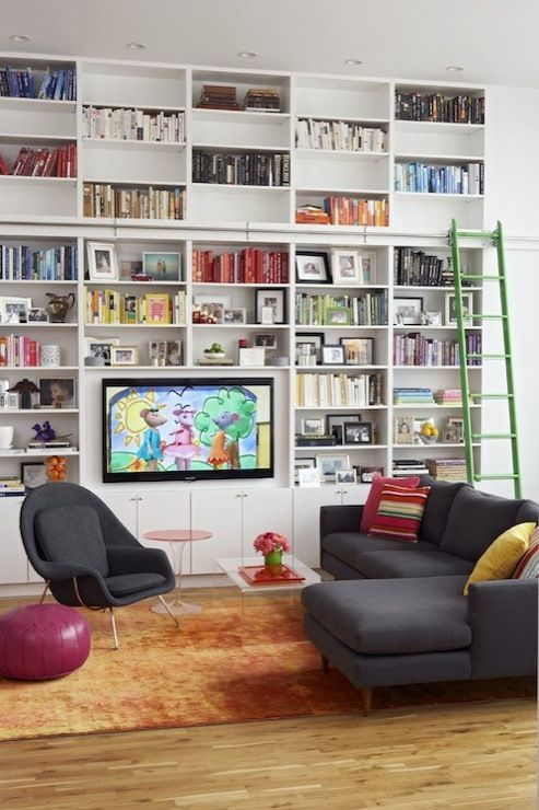 media rooms - Room Board Jasper Sectional Sofa with Chaise Lounge Saarinen Womb Chair CB2 Peekaboo Clear Coffee Table orange ombre rug acrylic round accent table fuchsia Moroccan leather pouf wall white modern built-ins bookshelves green ladder TV yellow red green pillows