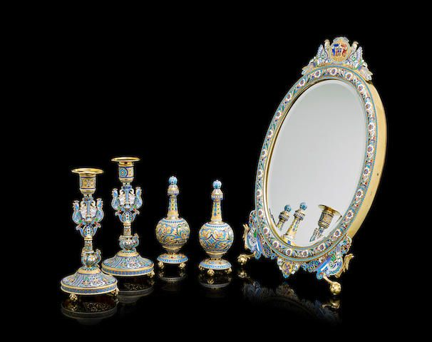 An important silver gilt and enamel dressing table set in the Russian style, Ovchinnikov, Moscow, 1889. Comprising an oval mirror richly decorated with floral garland and beaded border, surmounted with a coat-of-arms supported by two peacocks in heraldic potions, with Cyrillic monogram 'YO' flanked by two large mythical birds; with a pair of perfume bottles and candle holders decorated en suite with heraldic roosters, with foliate motifs, geometric borders, all in varicoloured filigree…