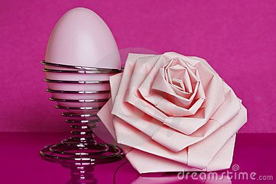 A pink egg and a pink paper rose on a pink background