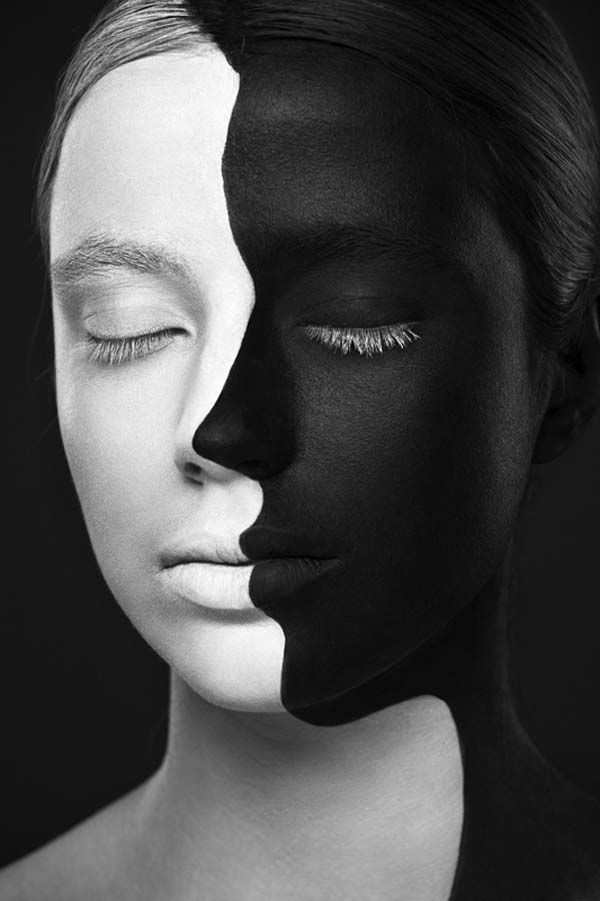This shows the principle contrast. Half of her face is white while the other half is black. Having the two opposite colors next to each other shows juxtaposition.