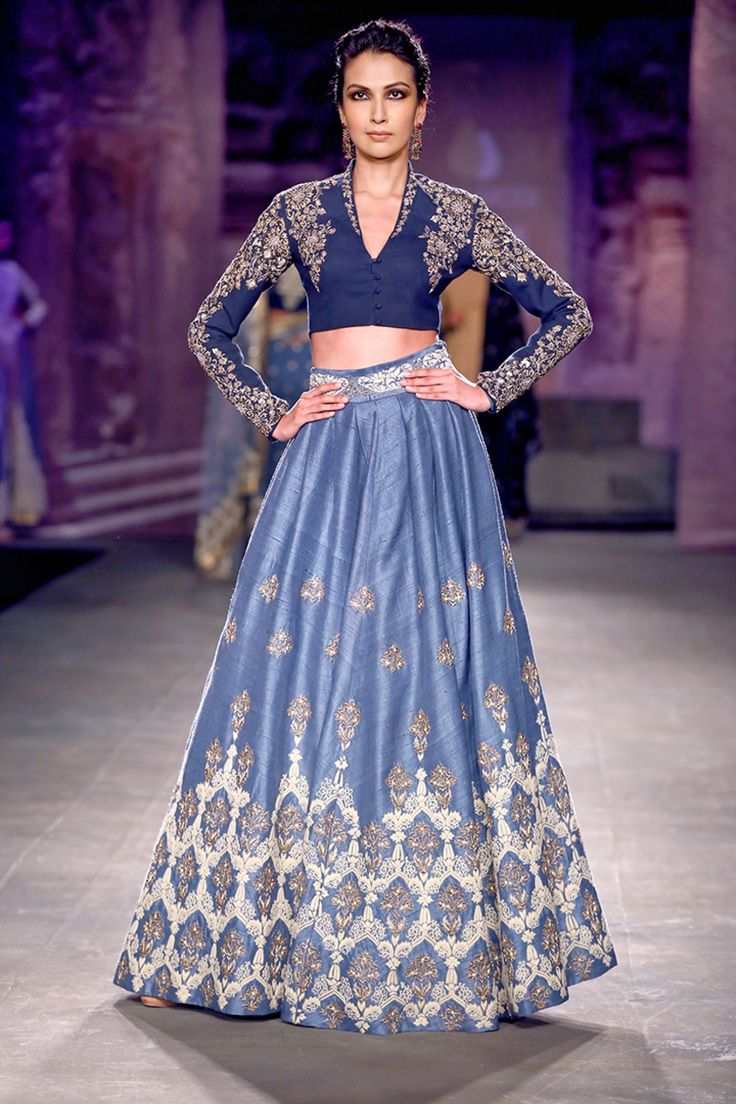 This lehenga is embroidered in silver zari and dabka in raw silk lehenga along with a golden blouse. This lehenga skirt is in powdered blue colour. Blouse is in navy blue colour with hand-embellished