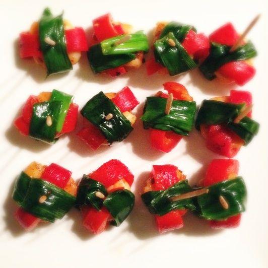 Recept voor garnalen hapjes in de vorm van cadeautjes. Gemarineerd met harissa en omwikkeld met gegrilde paprika en lente ui.