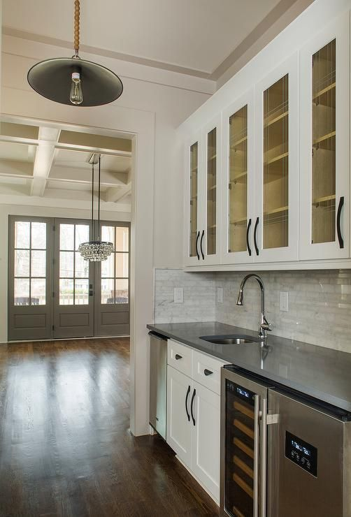 Cottage+butler's+pantry+features+glass+front+upper+cabinets+adorned+with+oil+rubbed+bronze+pulls+and+lower+cabinets+topped+with+gray+quartz+fitted+with+a+curved+sink+and+gooseneck+faucet+flanked+by+a+stainless+steel+mini+fridge+to+the+left+and+side+by+side+wine+coolers+to+the+right+illuminated+by+a+vintage+rope+barn+pendant.
