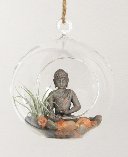 A small Buddha statue finds sanctuary in a hanging terrarium filled with smooth pebbles, sparkling crystal rocks and a relaxing air plant.