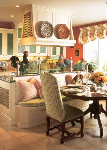 While island seating is a popular kitchen amenity, this island includes a furniture-look banquette for extra seating at a pedestal table. The banquette's middle-of-the-room location leaves clear routes to adjacent areas.