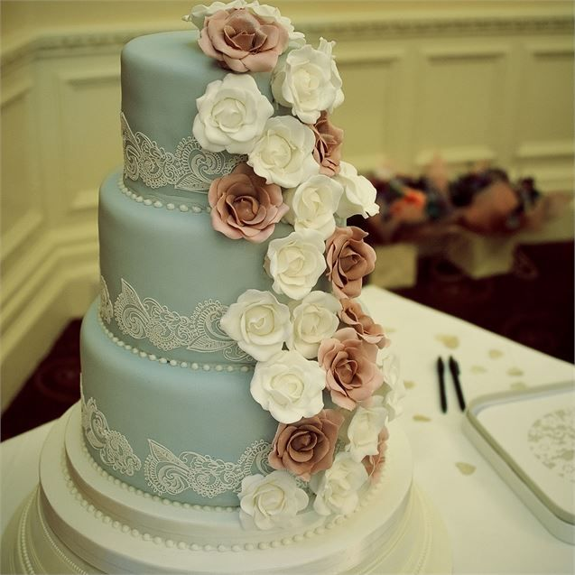 Sophie and Greg cut into a beautiful pastel blue wedding cake that matched the vintage wedding theme. The baby-blue cake was decorated with pink and white roses that cascaded down one side, and lace-like white icing on each of the tiers.The cake was created by Petra's Cakes and consisted of vanilla, lemon and chocolate flavoured tiers. It was served up after the wedding meal on the vintage cake plates the couple had sourced.After their romantic, vintage themed wedding, Greg and Sophie jetted…