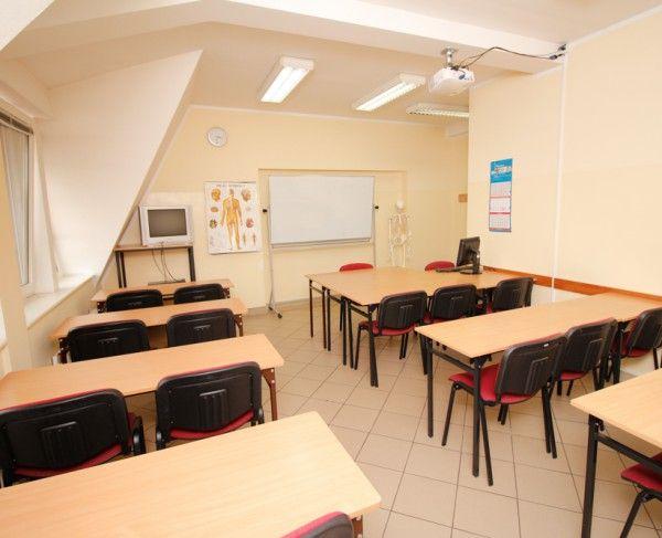 Sala szkoleniowa w Olsztynie, widok na ławki w układzie szkolnym, rzutnik, telewizor i DVD oraz tablice suchościeralną