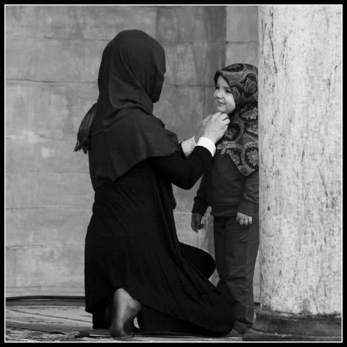 A mother adjusts the hijab of her young daughter before entering the mosque.