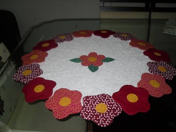 Centrinho em patchwork, tecido 100% algodão, com flores em volta ; estruturada com manta R2 e quilte livre (medindo 90 cm de diâmetro.)