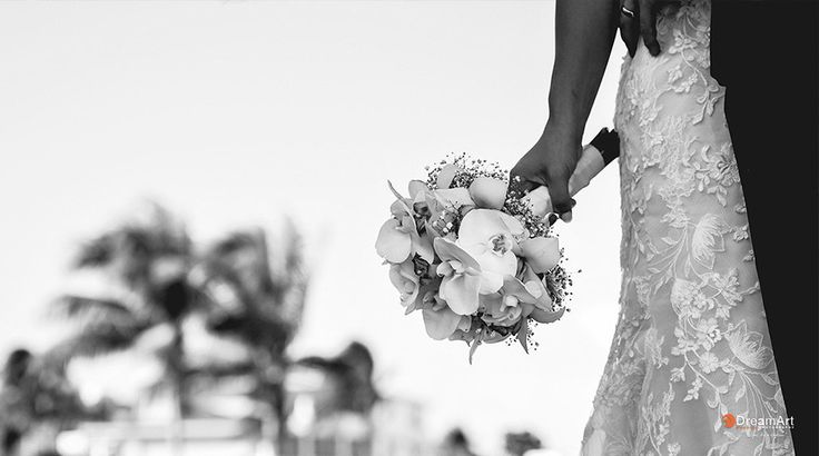 Close-up black and white photograph shows the details of bride's bouquet and embellished wedding dress | Palace Resorts Weddings ®