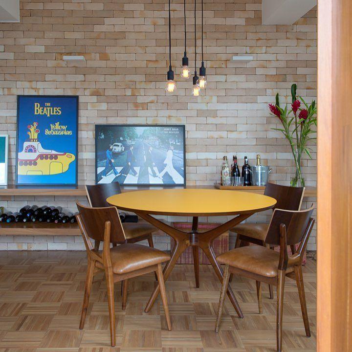 Sala de jantar com tijolinho e iluminação pendente - a mesa com tampo amarelo é quase um ponto de luz na sala  {Projeto Roberta Moura Paula Faria e Luciana Manbrini}