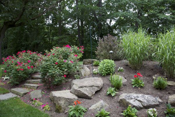 This picture shows a hillside professionally landscaped with steps, boulders, grasses, shrubs and a variety of perennials, turning a liability into a delight.