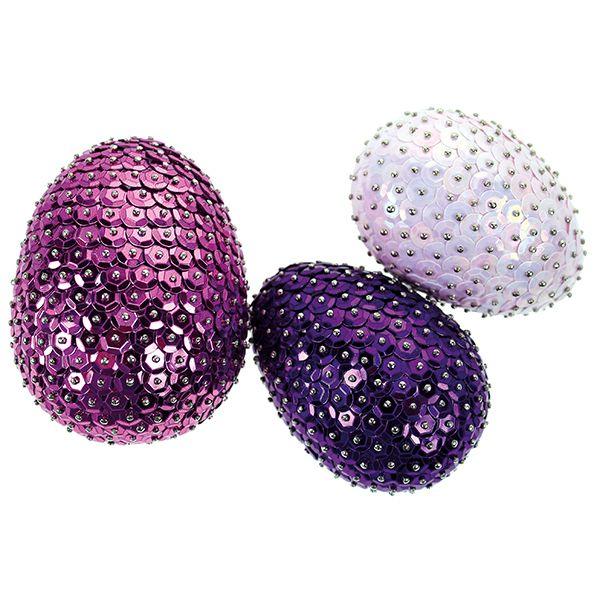 Paljettien ja somistusneulojen avulla valmistetut palejttimunat. Pohjalla styrox-munia.