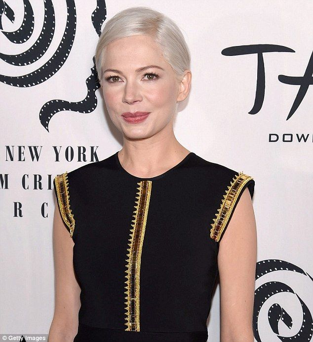 Style queen: The platinum blonde actress, 36, dazzled in a black dress with gold trim as she posed for photos on the red carpet ahead of the ceremony